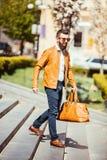 Красивый молодой бородатый человек в солнечных очках идя вниз на лестницы с сумкой на городе outdoors стоковая фотография rf