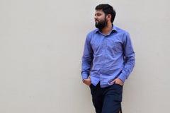 Красивый молодой бородатый человек на стоять против стены, портрета бородатого человека с руками в карманн & полагаться против ст Стоковое Изображение RF