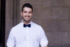 Красивый молодой бородатый человек с белыми рубашкой и бабочкой на улице Стоковое фото RF