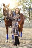 Красивый молодой женский идти и ласкать ее коричневую лошадь в сельской местности стоковое изображение rf