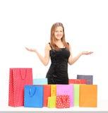 Красивый молодой женский представлять с много хозяйственных сумок на таблице Стоковое Фото