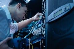Красивый молодой инженер исправляя кабельное соединение Стоковое Изображение