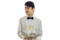 Красивый молодой кельнер повернул его голову и держать стекла шампанского на подносе то Стоковое Изображение