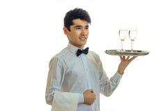 Красивый молодой кельнер усмехаясь и держа стекла шампанского на подносе то стоковое фото