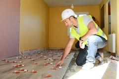 Красивый молодой мастер наблюдая место contruction плиток пола реновации дома Стоковые Фотографии RF