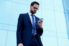 Красивый молодой менеджер крупной корпорации получал сообщение от босса на мобильном телефоне стоковая фотография