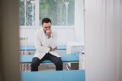 Красивый молодой доктор в белом пальто сидит уныло в больничной палате стоковая фотография