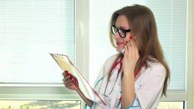 Красивый молодой доктор с папкой файла говоря на сотовом телефоне с ее пациентом акции видеоматериалы
