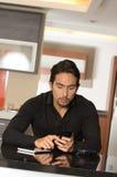 Красивый молодой профессионал используя сотовый телефон стоковые изображения rf