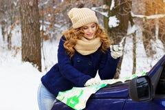 Красивый молодой усмехаясь чай девушки выпивая на bonnet автомобиля и смотреть в карте, нося синем пиджаке Девушка перемещения Стоковые Изображения