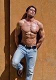 Красивый молодой человек без рубашки с джинсами против стены, глазами закрыл Стоковое Изображение