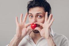 Красивый молодой человек брюнет в рубашке держит в сердце рук красном Стоковые Фотографии RF