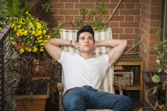 Красивый молодой человек в дн-мечтать балкона стоковое фото rf