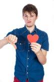 Красивый молодой человек в рубашке джинсовой ткани голубой стоя на белой предпосылке с красным бумажным сердцем в руках стоковое фото rf