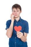 Красивый молодой человек в рубашке джинсовой ткани голубой стоя на белой предпосылке с красным бумажным сердцем в руках стоковое изображение