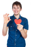 Красивый молодой человек в рубашке джинсовой ткани голубой стоя на белой предпосылке с красным бумажным сердцем в руках Стоковые Фотографии RF