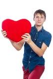 Красивый молодой человек в рубашке джинсовой ткани голубой стоя на белой предпосылке с красным бумажным сердцем в руках Стоковая Фотография