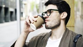 Красивый молодой человек в стеклах выпивая кофе и ждать в крупном плане улицы сток-видео