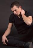 Красивый молодой человек в черноте Стоковые Изображения