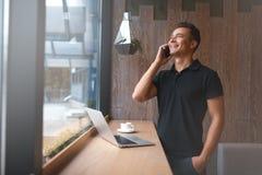 Красивый молодой человек говоря на телефоне и усмехаться стоковое изображение rf