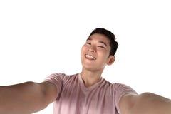 Красивый молодой человек держа камеру и делая selfie стоковые фотографии rf