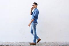 Красивый молодой человек идя и говоря на сотовом телефоне Стоковое Изображение RF