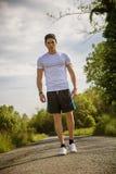 Красивый молодой человек идя и trekking на дороге Стоковое Изображение