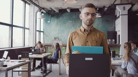 Красивый молодой человек получая увольнянный от работы Унылый мужчина идет через офис, нося коробку с личными вещами акции видеоматериалы