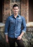 Красивый молодой человек при рубашка джинсовой ткани стоя outdoors, усмехающся стоковые изображения rf