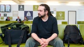 Красивый молодой человек при dreadlocks ждать на салоне авиапорта Стоковые Фотографии RF