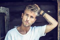 Красивый молодой человек против деревянной стены планок Стоковое фото RF