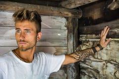 Красивый молодой человек против деревянной стены планок Стоковое Изображение