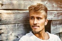 Красивый молодой человек против деревянной стены планок Стоковые Фото