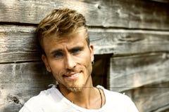 Красивый молодой человек против деревянной стены планок Стоковая Фотография