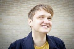 Красивый молодой человек против усмехаться кирпичной стены стоковые изображения rf