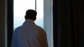 Красивый, молодой человек раскрывает занавес Стоящ и смотрящ вне окно движение медленное видеоматериал