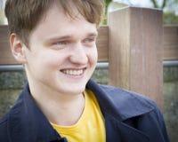 Красивый молодой человек сидя на усмехаться стенда стоковое изображение