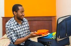 Красивый молодой человек сидя на чемодане упаковки кровати и усмехаясь, концепция гостя общежития Стоковое Изображение RF