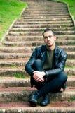 Красивый молодой человек сидя на шагах outdoors стоковые фотографии rf