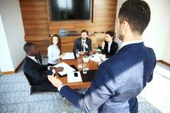 Красивый молодой человек стоя близко whiteboard и указывая на диаграмму пока его сотрудники слушая и сидя на Стоковые Изображения