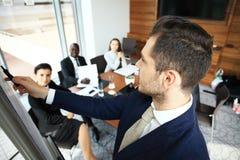 Красивый молодой человек стоя близко whiteboard и указывая на диаграмму пока его сотрудники слушая и сидя на Стоковое фото RF