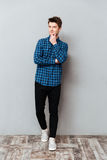 Красивый молодой человек стоя над серой стеной и представлять стоковое фото