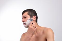 Красивый молодой человек с сериями крема для бритья на его сторона prepar Стоковое Изображение