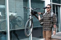 Красивый молодой человек с стеклами носит велосипед на его концепции образа жизни плеча ежедневной по заведенному порядку стоковые изображения rf