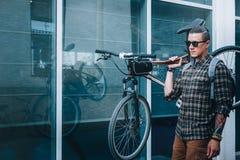 Красивый молодой человек с стеклами носит велосипед на его плече Стоковые Фотографии RF