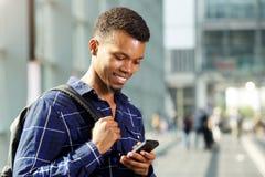 Красивый молодой человек усмехаясь и используя умный телефон стоковые изображения rf