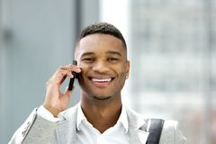 Красивый молодой человек усмехаясь с мобильным телефоном Стоковое Изображение RF