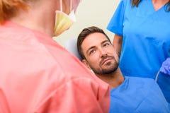 Красивый мужской пациент ждать для того чтобы получить зубоврачебную обработку в зубоврачебной студии Стоковое Фото