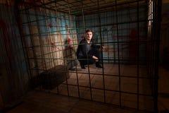 Красивый мужчина заключенный в турьму в клетке металла при splattered кровь Стоковое фото RF