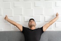 Красивый мужчина протягивает руки после сна на утре стоковое изображение
